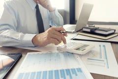 Работа бизнесмена с компьютером на таблице в конторской работе с pape Стоковое Фото