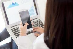 Работа бизнес-леди крупного плана с анализом финансового состояния и строгая данными на компьтер-книжке, девушке держа умный моби Стоковое фото RF