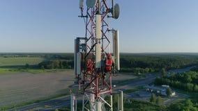 Работа большой возвышенности, техник служит антенны мобильной телефонии, интернет, телевидение на предпосылке акции видеоматериалы