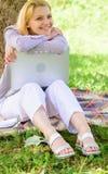 Работа девушки с ноутбуком в парке сидеть на траве Офис окружающей среды Женщина с ноутбука работы деревом outdoors постным стоковые фото