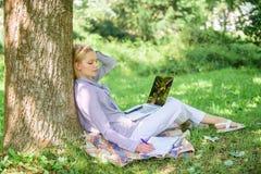 Работа девушки с ноутбуком в парке сидеть на траве E r Женщина с ноутбуком стоковая фотография rf