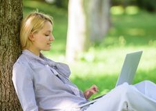 Работа девушки с ноутбуком в парке сидеть на траве E r Технология образования и стоковая фотография