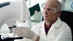 Работа доктора микробиологии с микроскопом в лаборатории акции видеоматериалы