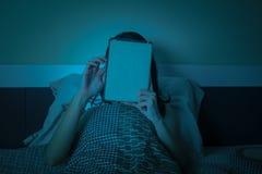 Работа женщины с таблеткой или компьютером на кровати на ноче Стоковая Фотография
