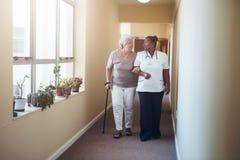 Работа здравоохранения помогая женскому пациенту стоковое изображение rf