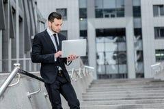 Работа и отдых Молодой человек работая на компьютере и выпивать Стоковые Фото