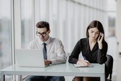 работа команды Красивый бизнесмен работая на компьтер-книжке пока бизнес-леди звоня телефонный звонок в современном офисе Стоковая Фотография