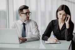 работа команды Красивый бизнесмен работая на компьтер-книжке пока бизнес-леди звоня телефонный звонок в современном офисе Стоковые Фотографии RF