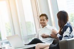 Работа компьтер-книжки пользы 2 азиатская сотрудников совместно имея кофе в af Стоковое фото RF