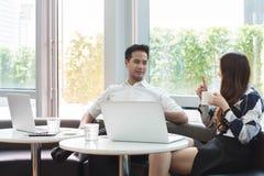 Работа компьтер-книжки пользы 2 азиатская сотрудников совместно имея кофе в af Стоковые Изображения RF