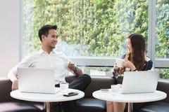Работа компьтер-книжки пользы 2 азиатская сотрудников совместно имея кофе в af Стоковое Изображение RF