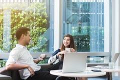 Работа компьтер-книжки пользы 2 азиатская сотрудников совместно имея кофе в af Стоковая Фотография RF