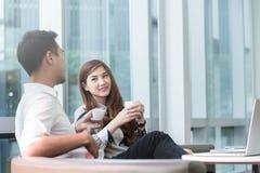 Работа компьтер-книжки пользы 2 азиатская сотрудников совместно имея кофе в af Стоковое Изображение