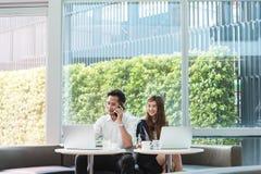 Работа компьтер-книжки пользы 2 азиатская сотрудников совместно Стоковые Изображения