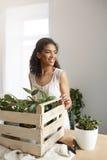 Работа красивой африканской девушки усмехаясь с заводами в коробке на рабочем месте огородите белизну Стоковое Изображение RF
