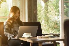Работа красивой молодой подростковой женщины независимая с ноутбуком на кофейне внутри со светом солнца стоковые фотографии rf