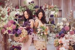 Работа красивых азиатских флористов женщин счастливая в магазине цветка с много весной цветет Стоковая Фотография