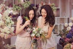 Работа красивых азиатских флористов женщин счастливая в магазине цветка с много весной цветет Стоковые Изображения