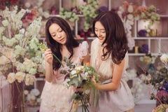 Работа красивых азиатских флористов женщин счастливая в магазине цветка с много весной цветет Стоковое фото RF