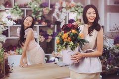 Работа красивых азиатских флористов женщин счастливая в магазине цветка с много весной цветет Стоковые Фото