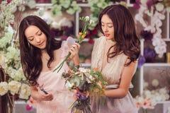 Работа красивых азиатских флористов женщин счастливая в магазине цветка с много весной цветет Стоковое Фото