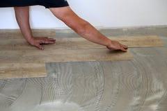 Работа на класть настил Работник устанавливая новый плиточный пол винила стоковое фото