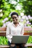 Работа на проломе Молодая Афро-американская женщина с ноутбуком сидит на деревянной скамье жизнерадостная милая черная девушка на стоковое фото