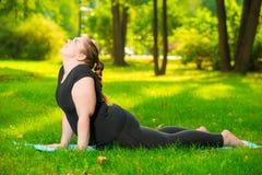 работа на себе - женщина спорт плюс размер в парке выполняет протягивать стоковая фотография rf