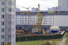 Работа на строительной площадке Бригада ` работников устанавливает кран башни Тяжелые работы строительной техники Стоковые Изображения