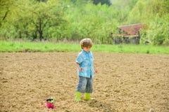 Работа на ферме Концепция матушка-природы Засаживать саженцы Ребенок имея потеху с меньшими лопаткоулавливателем и заводом в баке стоковые фото