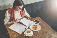 Работа онлайн, студент девушки делая домашнюю работу На чашке чаю таблицы, печенья, smartphone Обучение по Интернетуу Стоковое Фото