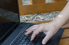 Работа оператора на открытом портативном компьютере на деревянной скамье стоковое изображение rf