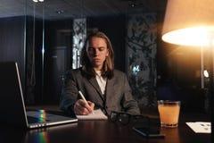 Работа отростчатая на современном офисе ночи Молодая работа сотрудника в coworking студии Бизнесмен использует современный компью стоковые фото