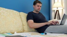 Работа от дома независимого Человек на софе печатает на компьтер-книжке акции видеоматериалы