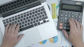 Работа рук бизнесмена с калькулятором и печатать на клавиатуре портативного компьютера акции видеоматериалы