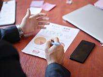 Работа рук ` s людей с документами на деревянном столе владение домашнего ключа принципиальной схемы дела золотистое достигая неб Стоковые Изображения RF