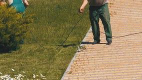Работа садовников косит траву с электрической травокосилкой видеоматериал