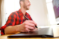 Работа среднего возраста дизайнерская на настольном компьютере с ручкой грифеля Стоковое Изображение