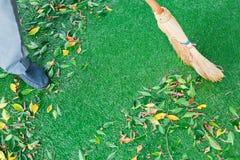 Работа с веником подметает лужайку от упаденных листьев стоковые фотографии rf