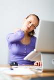 Работа слишком трудно- молодой женщины работая на компьютере стоковая фотография