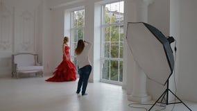 Работа фотографа с моделью в студии подпорки сток-видео