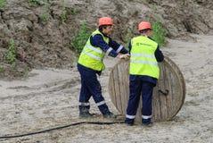 2 работника вытягивая кабельную линию связи высокого напряжения крена Стоковые Изображения