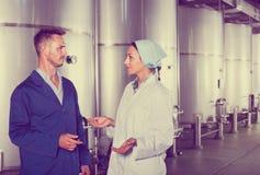 2 работника в защитной форме говоря в вторичном fermentat Стоковое Фото