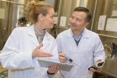 2 работника в формах на производственной линии в заводе Стоковое Изображение RF