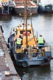 2 работника закрепили корабль к крану Стоковая Фотография