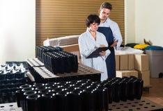2 работника контролируя количество бутылок вина на игристом вине Стоковые Фото