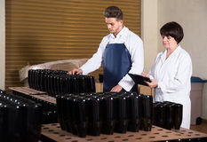 2 работника контролируя количество бутылок вина на игристом вине Стоковое Изображение RF