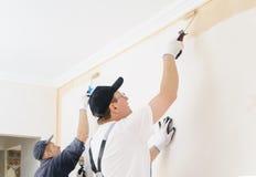 2 работника красят стену в комнате Стоковое Изображение