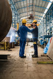 2 работника нося желтую трудную шляпу и голубую форму Стоковое Изображение