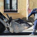 2 работника дороги в прозодеждах брызгают яму на дороге с мякишем асфальта перед выравнивать ремонтируя дорогу Стоковое Изображение RF
